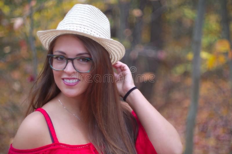 Young woman hat glasses autumn red dress orange forest portrait royalty free stock photos