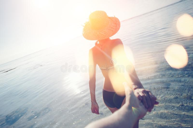 Young woman in hat guiding a man by the hand into the ocean royalty free stock photography