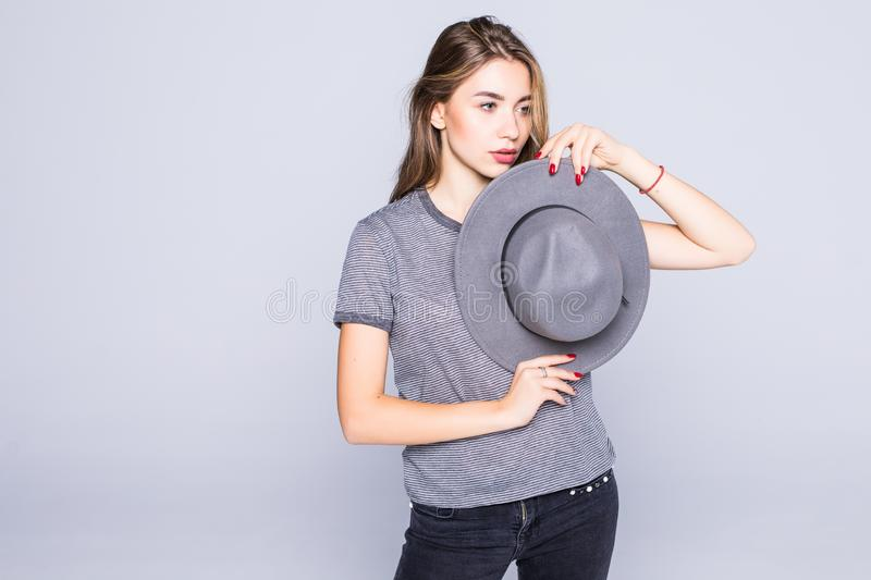 Young woman with hat in hands possing on gray background stock images