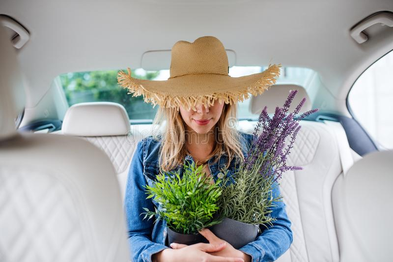 Young woman with hat and plants sitting in car, having fun. stock photos