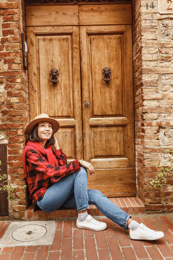 young woman with hat posing near wooden door in old italian tuscany town royalty free stock image