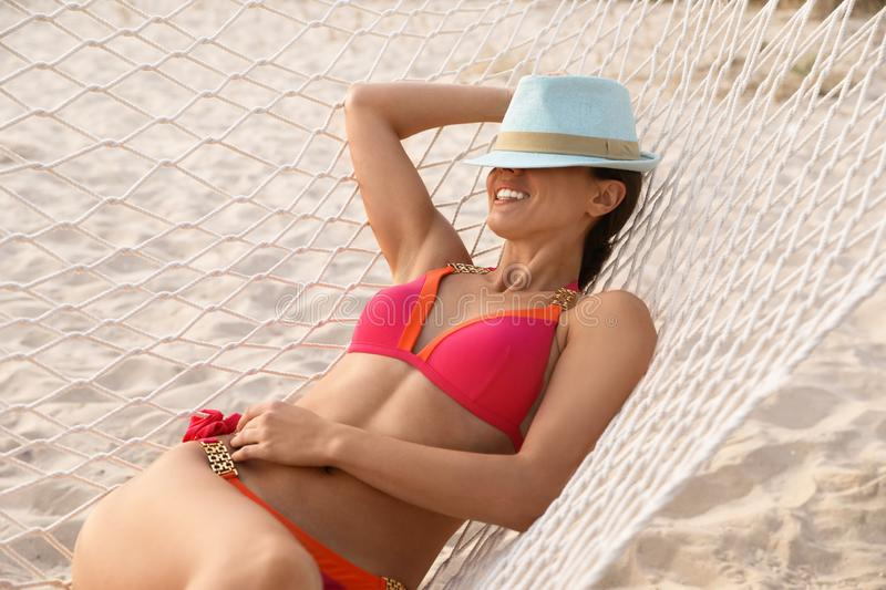 Young woman with hat relaxing in hammock on. Beach stock images