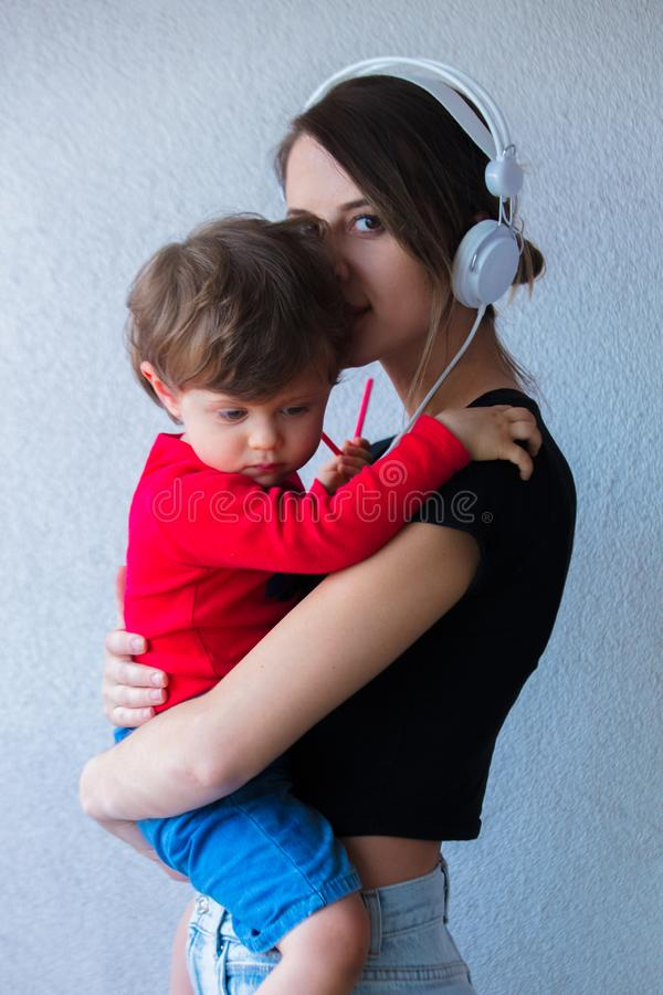 Young woman in hat and 90s style clothes and little toddler boy royalty free stock photography