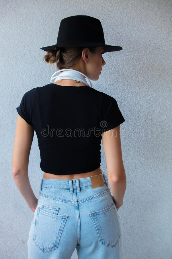 Young woman in hat and 90s style clothes royalty free stock photo