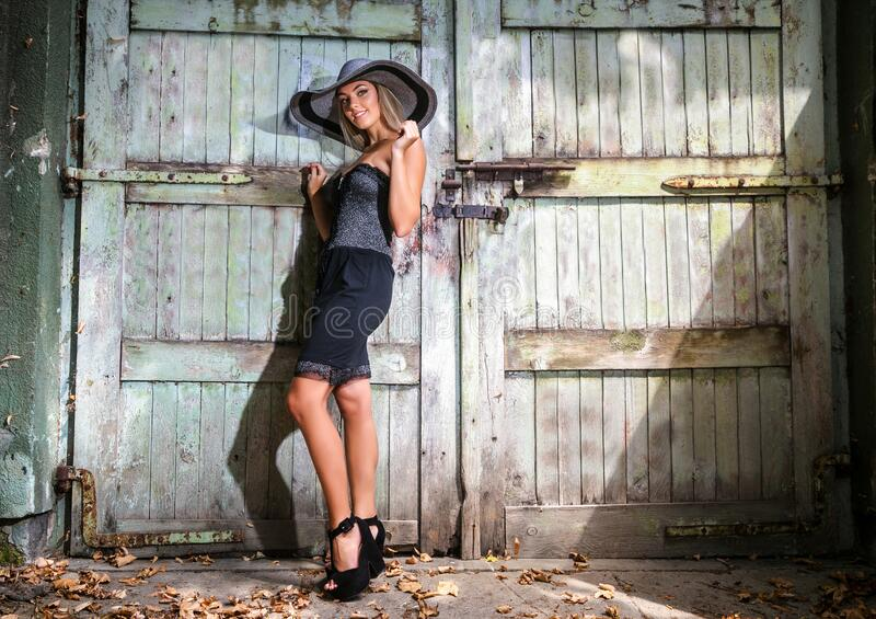Beautiful woman with hat in short black summer dress royalty free stock image