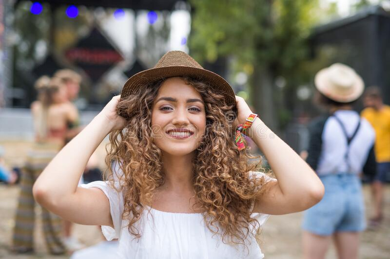 Young woman with hat at summer festival, looking at camera. royalty free stock photography