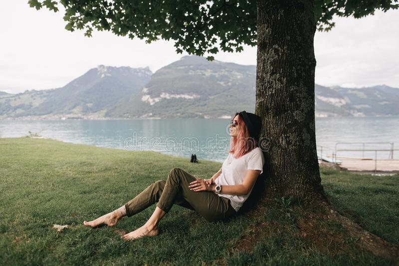 young woman in hat and sunglasses sitting and leaning at tree near beautiful mountain lake in Bern stock photo