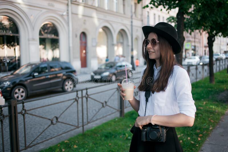 Young woman in hat walking in city. Girl tourist enjoys the walk. royalty free stock photo