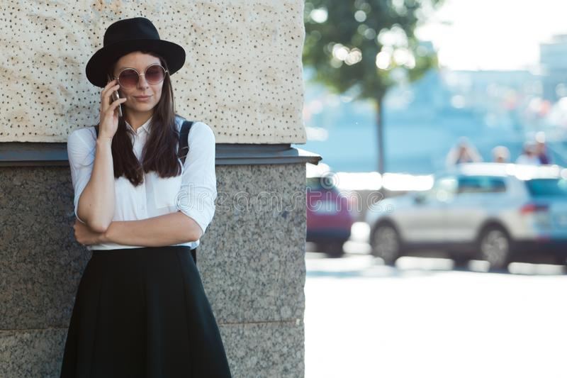 Young woman in a hat and a white shirt walks in the city and uses a smartphone. royalty free stock photo
