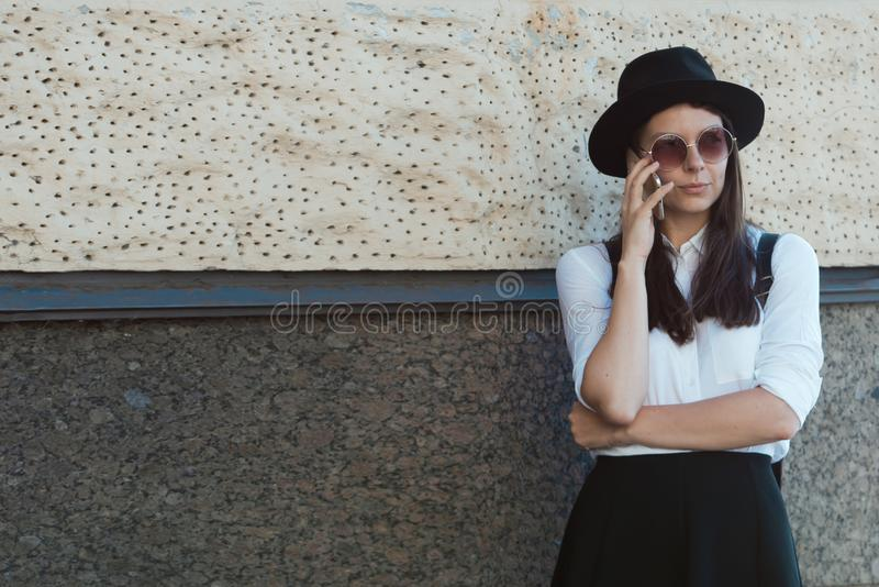 Young woman in a hat and a white shirt walks in the city and uses a smartphone. stock image