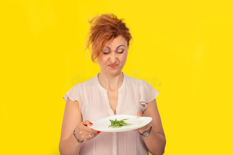 Young woman hates vegetarian diet. A mature 40 years old woman hates her vegetarian diet concept. Woman looking with disgust to the green salad on her plate royalty free stock image