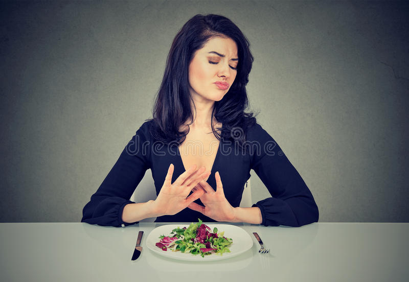 Young woman hates vegetarian diet. Rejects green salad royalty free stock photo