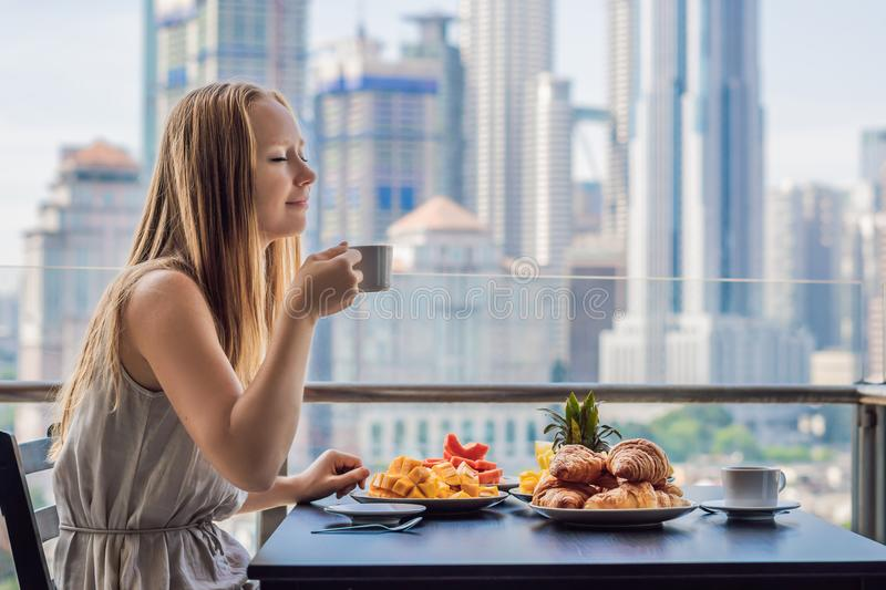 A young woman is having breakfast on the balcony. Breakfast table with coffee fruit and bread croisant on a balcony against the b. Ackdrop of the big city royalty free stock photography