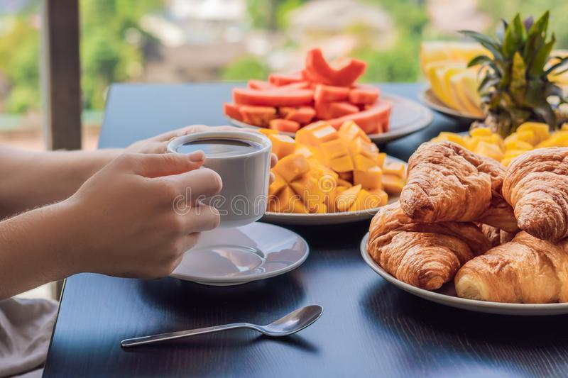 A young woman is having breakfast on the balcony. Breakfast table with coffee fruit and bread croisant on a balcony. Against the backdrop of the big city royalty free stock photography