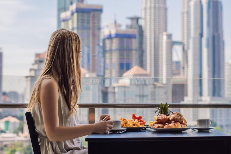 A young woman is having breakfast on the balcony. Breakfast table with coffee fruit and bread croisant on a balcony. Against the backdrop of the big city stock photos
