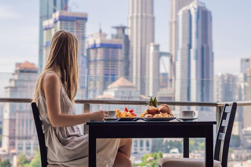 A young woman is having breakfast on the balcony. Breakfast table with coffee fruit and bread croisant on a balcony. Against the backdrop of the big city royalty free stock photo