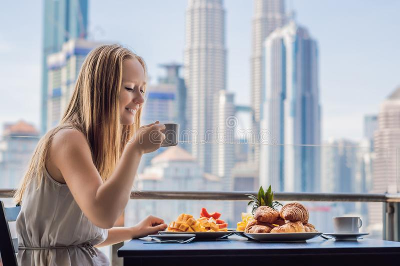 A young woman is having breakfast on the balcony. Breakfast table with coffee fruit and bread croisant on a balcony. Against the backdrop of the big city stock photo