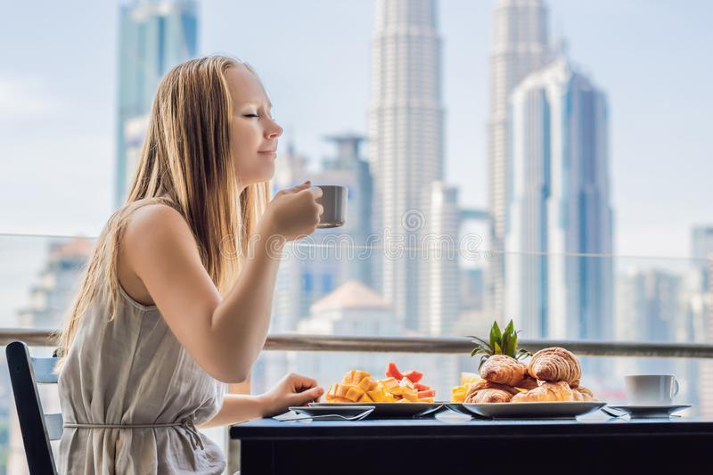 A young woman is having breakfast on the balcony. Breakfast table with coffee fruit and bread croisant on a balcony. Against the backdrop of the big city stock images
