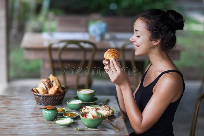 Young woman enjoying breakfast and holding croissant in hand. Young woman having breakfast and holding croissant in hand. Morning good mood stock photography