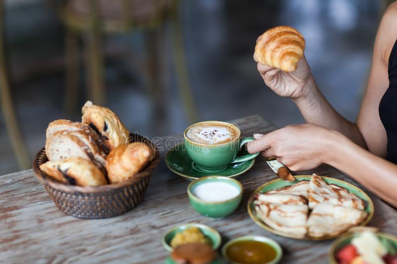 Young woman enjoying breakfast and holding croissant in hand. Young woman having breakfast and holding croissant in hand. Morning good mood royalty free stock photos