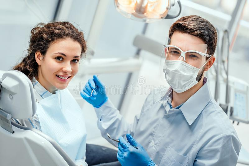 Young woman having check up and dental exam at dentist. Side view stock photography