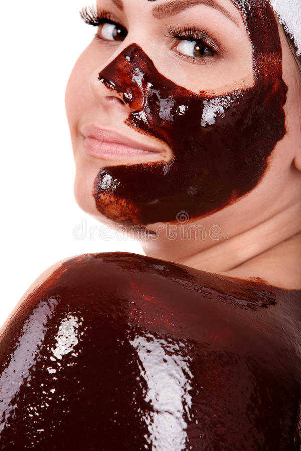 Young woman having chocolate facial mask. stock photography