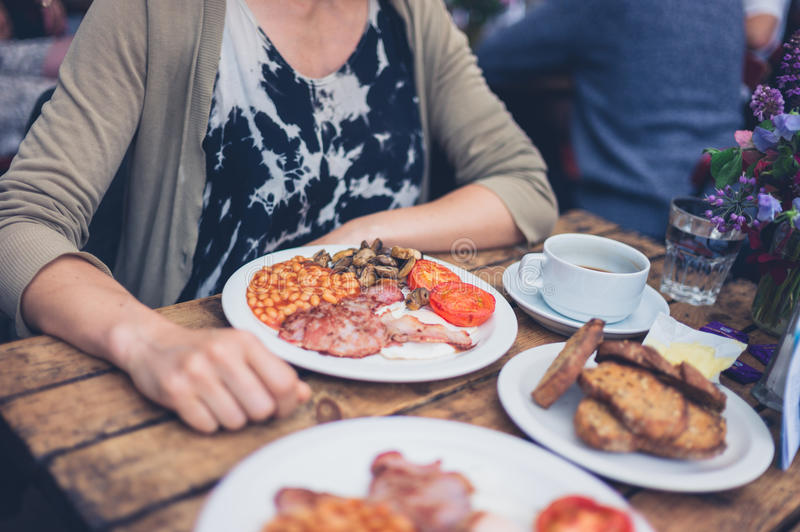 Young woman having an english breakfast. A young woman is having a traditional english breakfast in a cafe stock photos