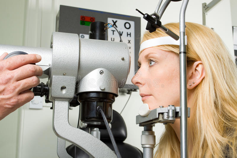Young woman having eye test. Attractive young woman having an eye sight examination at an optician's clinic stock image