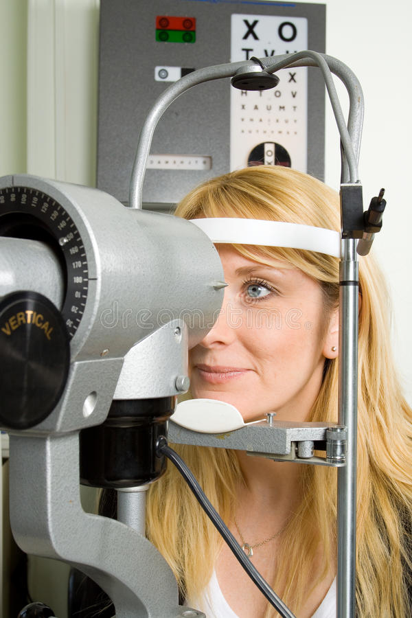 Young woman having eye test. Attractive young woman having an eye sight examination at an optician's clinic royalty free stock image