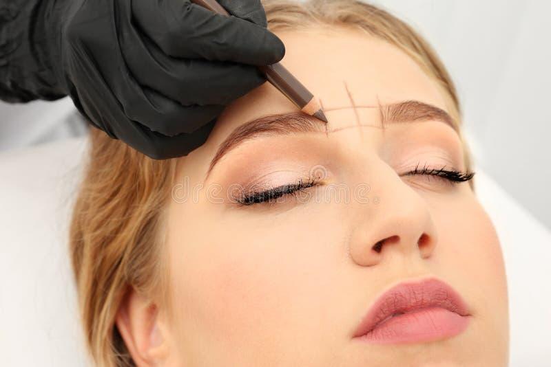 Young woman having eyebrow correction procedure royalty free stock photography