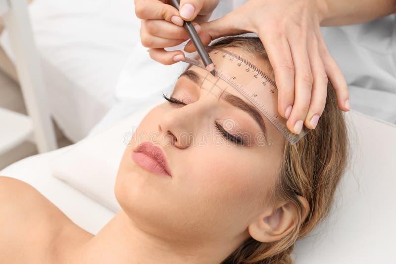 Young woman having eyebrow correction procedure stock photos