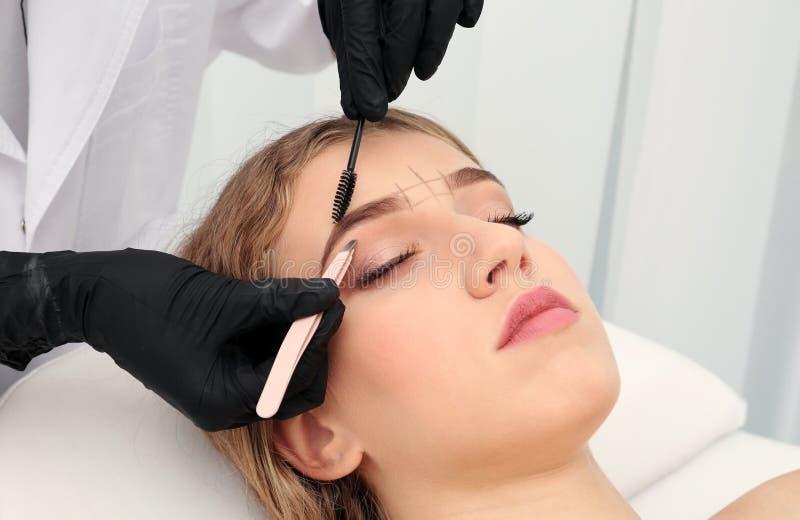 Young woman having eyebrow correction procedure stock photography