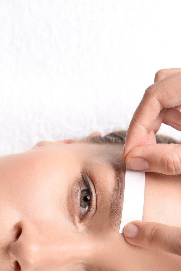 Young woman having eyebrow correction procedure. In beauty salon, closeup royalty free stock image