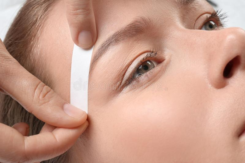 Young woman having eyebrow correction procedure. In beauty salon, closeup royalty free stock images