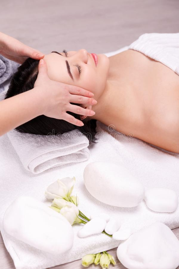 Young woman having face massage in spa stock photography