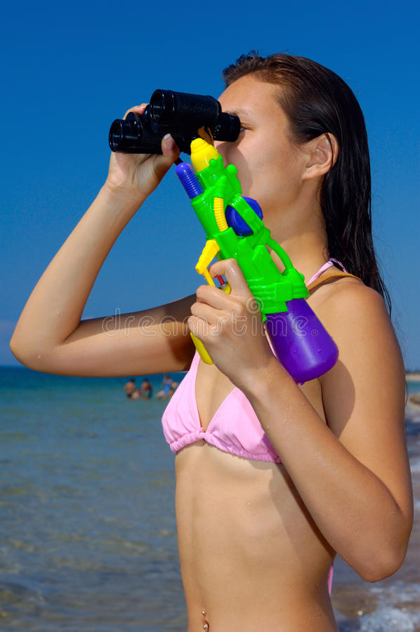 Young Woman Having Fun at the Beach. Woman with water-pistol looking through binocular at the beach stock images