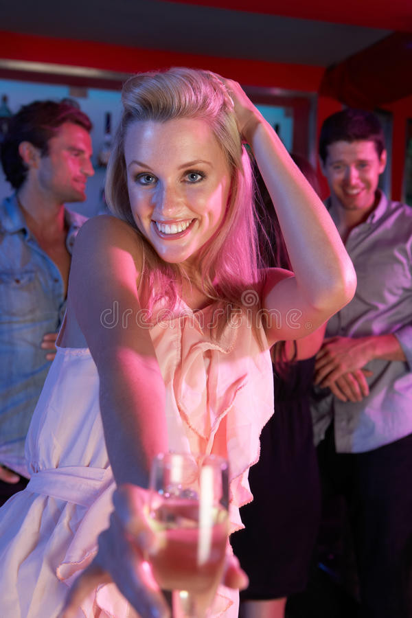 Young Woman Having Fun In Busy Bar stock photography