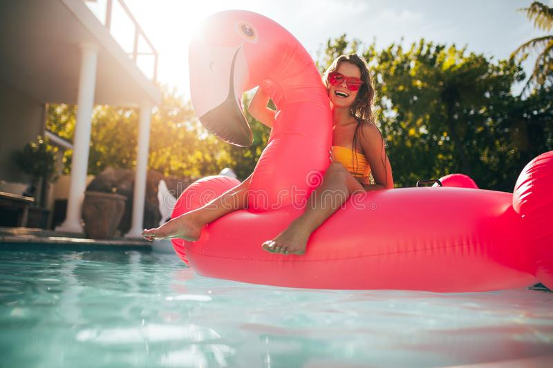 Woman having fun on an inflatable pool float mattress stock image