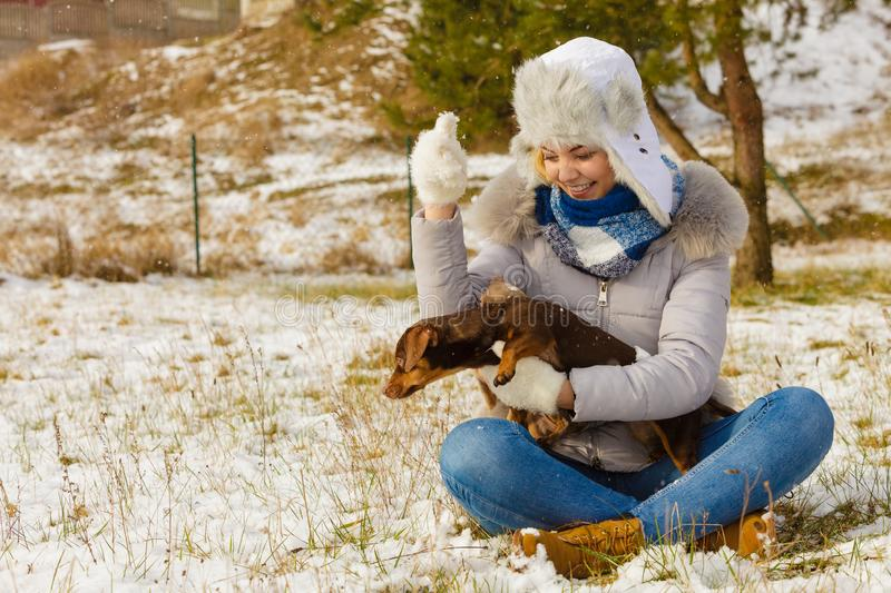 Woman playing with dog during winter stock image