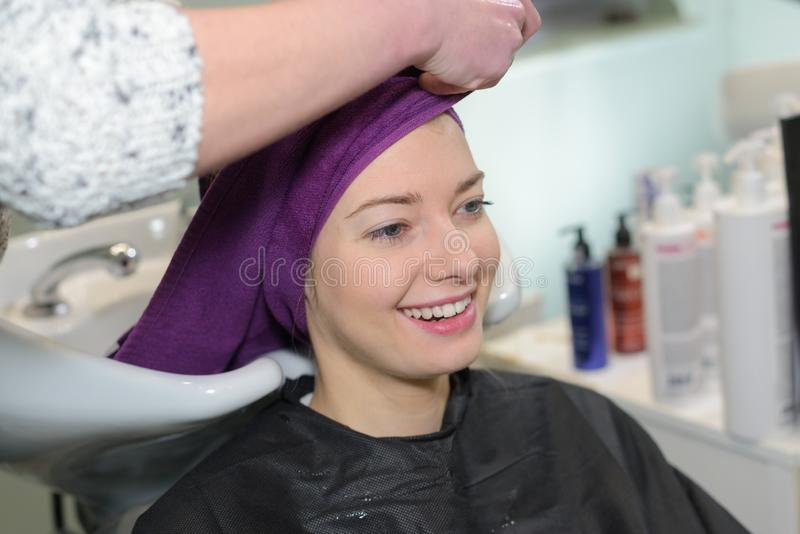 Young woman having hair washed by stylist in salon. Woman royalty free stock photography