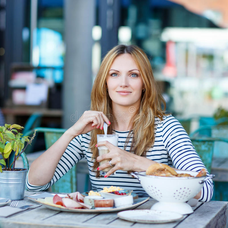 Young woman having healthy breakfast in outdoor cafe royalty free stock image