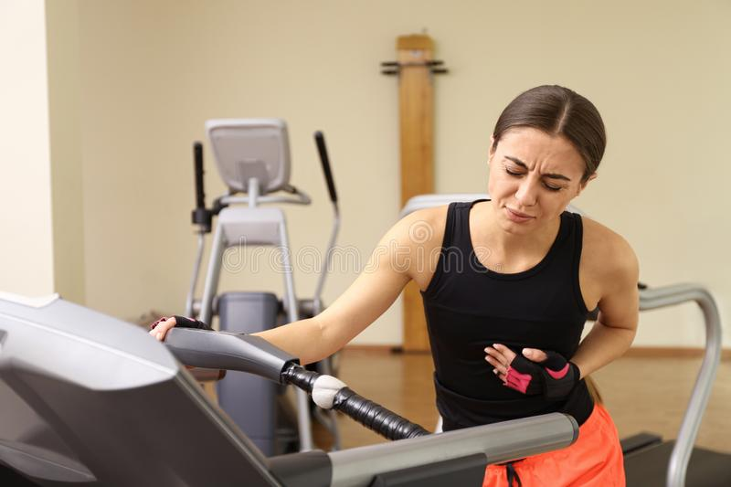 Young woman having heart attack on treadmill royalty free stock photo