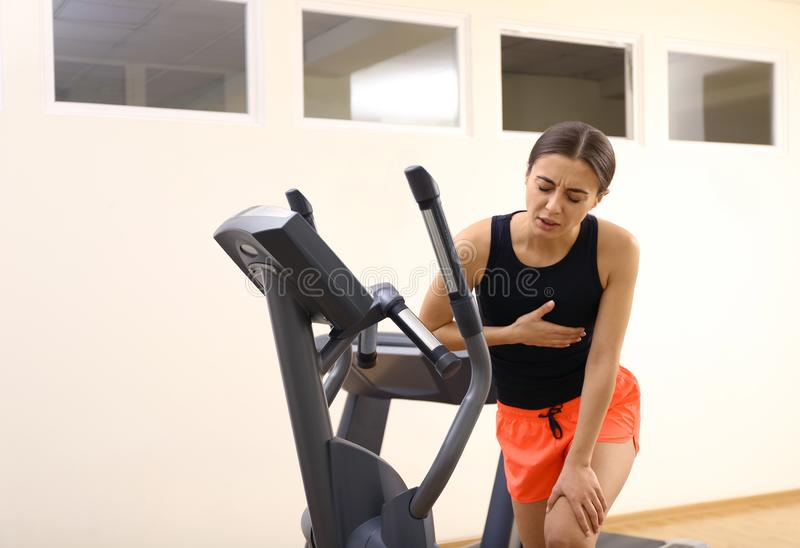 Young woman having heart attack on treadmill stock images