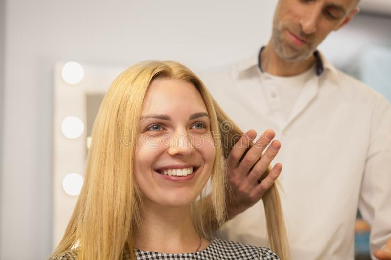 Young woman having her hair styled by hairdresser stock photo