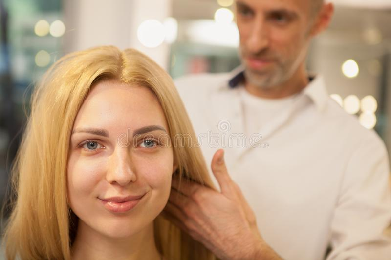 Young woman having her hair styled by hairdresser royalty free stock images