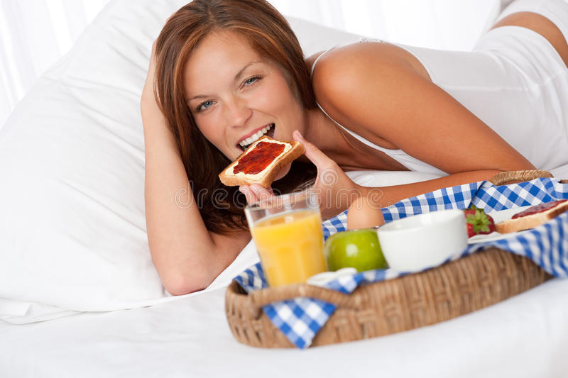 Young woman having home made breakfast. In bed stock photography