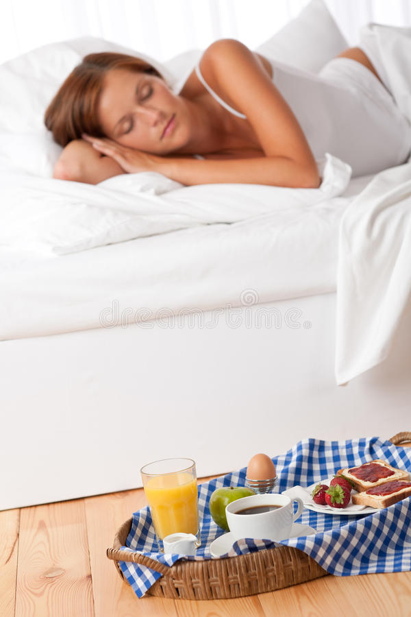 Young woman having home made breakfast. In bed, sleeping royalty free stock photography