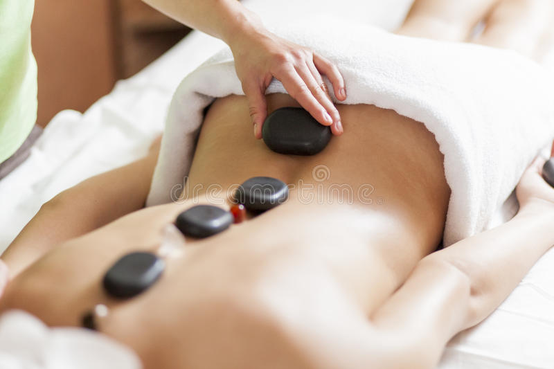 Young woman having a hot stone massage therapy. Woman having a hot stone massage therapy royalty free stock image