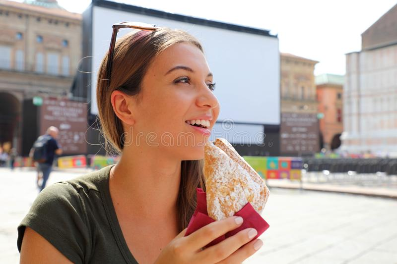 Young woman having italian breakfast with croissant and coffee at the cafe on the street.  stock photos
