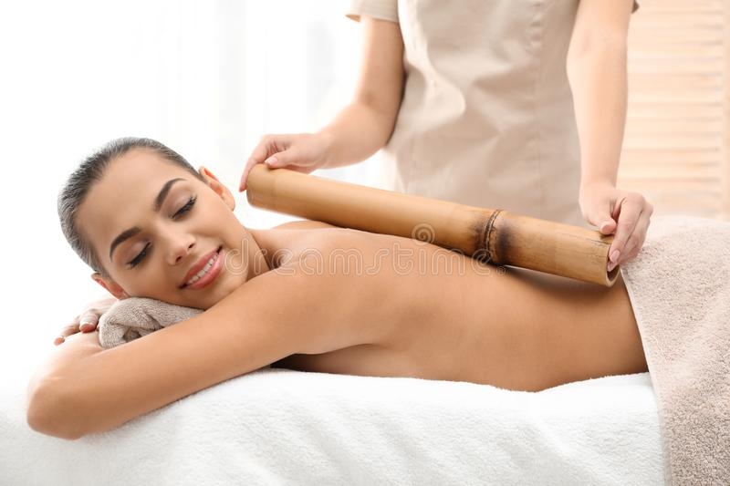 Young woman having massage with bamboo stick. In wellness center stock images
